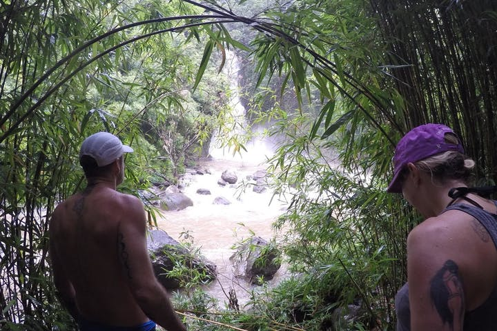 A couple hiking in Hana, surrounded by green vegetation and approaching a waterfall