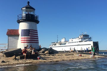 Photo of beach with lighthouse near Cape Cod with large boat in background