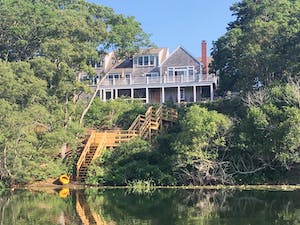 Large Cape Cottage styled house sitting back from river