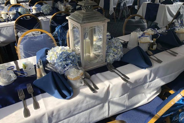 Table display for a wedding with white table clothes and blue napkins and flower decor