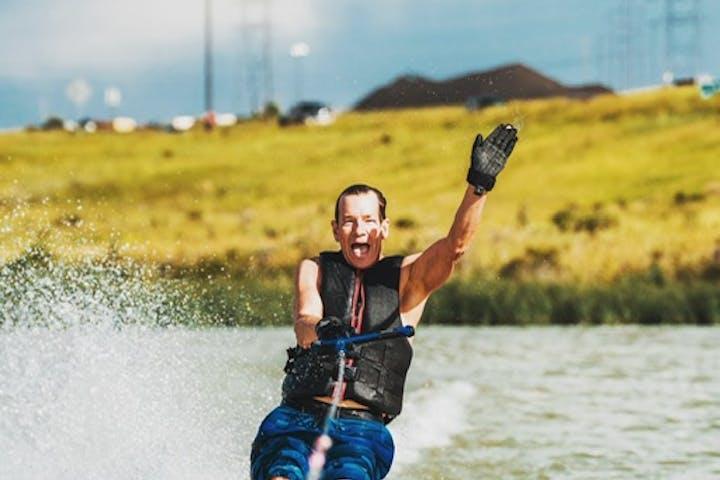 man waving while skiing