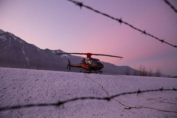 helicopter on the snow with sunset in background