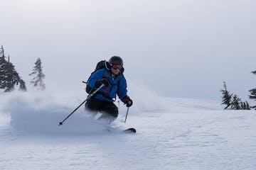 man skiing in blue jacket