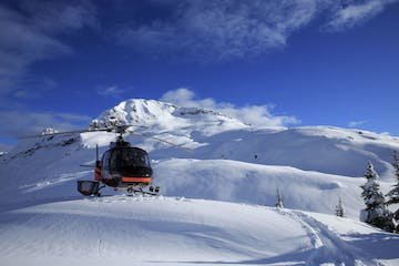 helicopter landing in snow on top of mountain