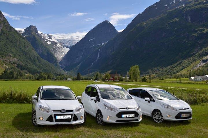 Three white car in a green field