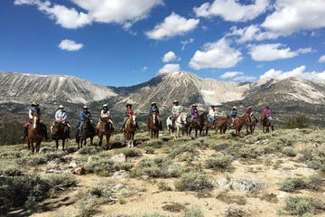 group of horseback riders on horses with mountains in background