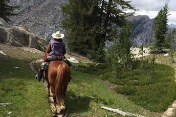 horseback riders with mountains and trees