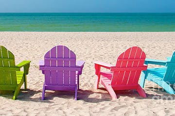 Brightly colored beach chairs on the beach facing the green and blue ocean