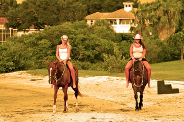 Two guides riding horses on the beach in Florida