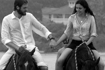 Man and woman holding hands on horseback