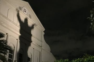 The shadow of a statue on the side of a building