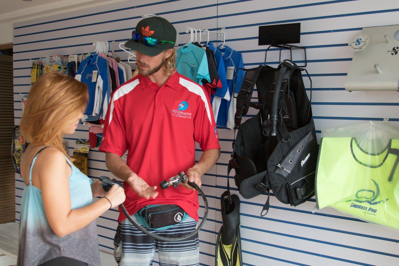 Aqua Adventures sells representative showing customer a regulator for scuba diving