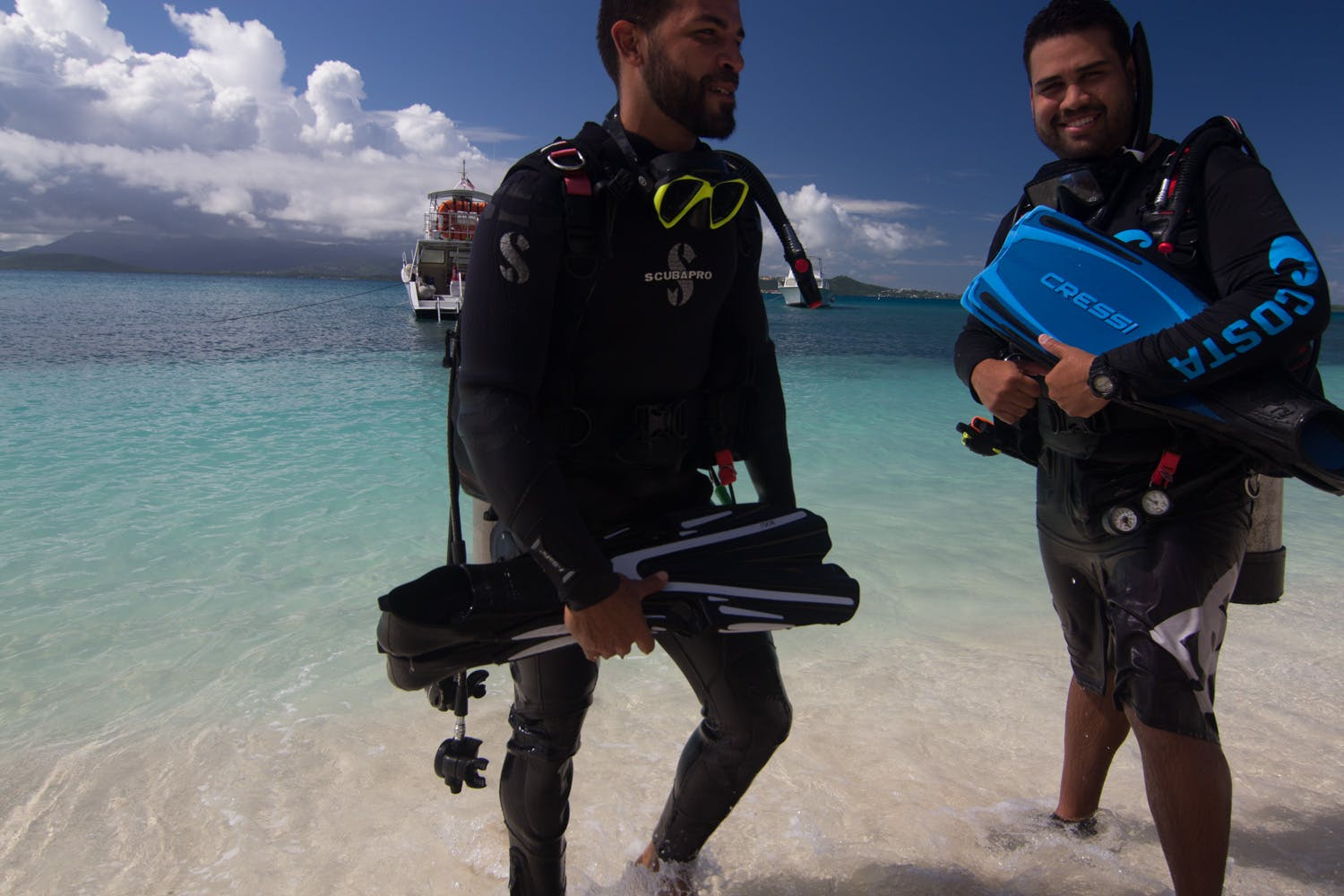 Scuba divers with equipment emerging from the beach