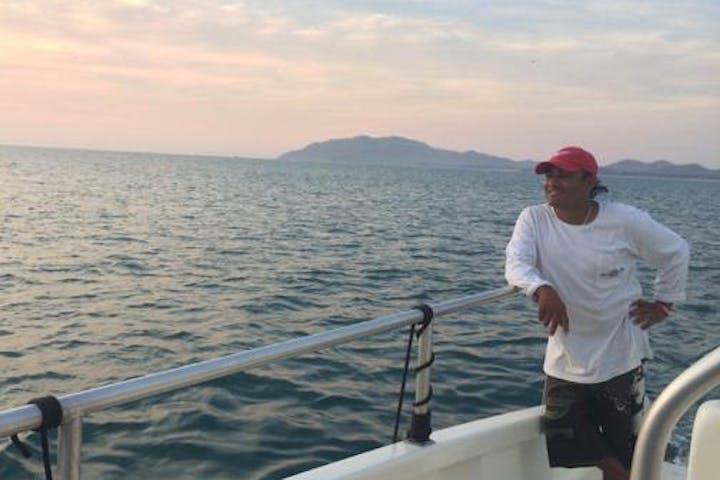 man next to railing on catamaran