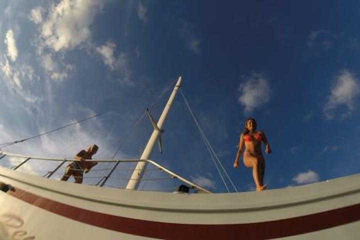 Girl jumping off of catamaran