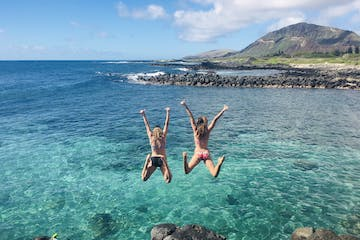 Two girls jumping off a cliff into the ocean in Hawaii