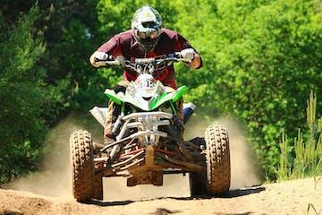 a man flying through the air while riding a bike down a dirt road