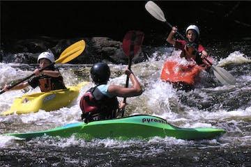 3 kids paddling down whitewater river