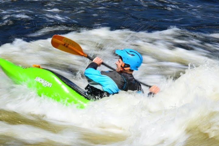man wearing blue gear in a green kayak