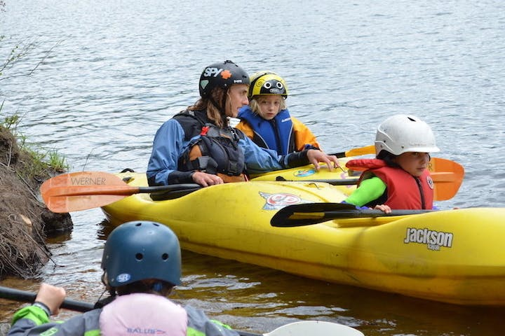 2 kids learning how to kayak