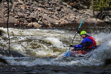 man in single kayak going down whiteriver