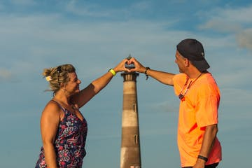 Couple making heart in front of lighthouse