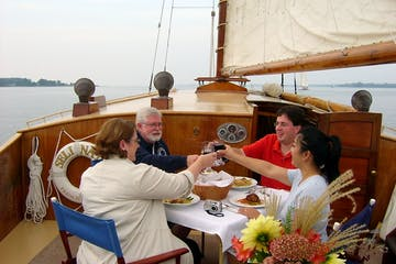 group having dinner and toasting on the sail boat