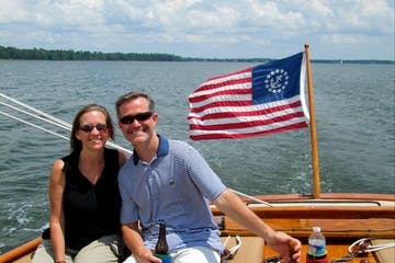 couple enjoying beverages on the front of the sailboat