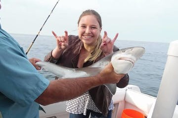Woman posing with shark that she caught