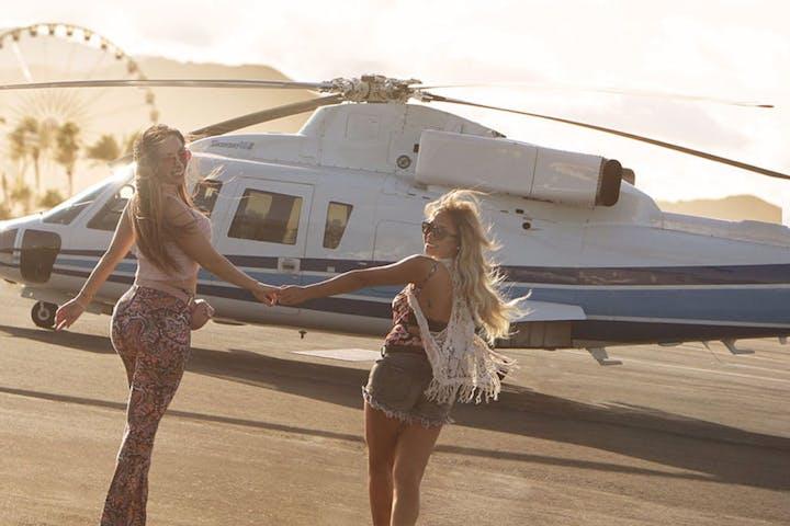 Two women walking toward helicopter on landing pad near the beach