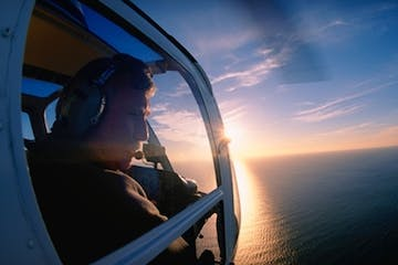 Person looking out helicopter window over the ocean at sunset