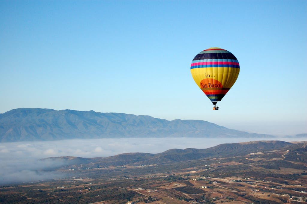 a large balloon in the air with a mountain in the... </p srcset=