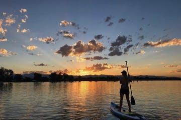 person paddle boarding at sunset