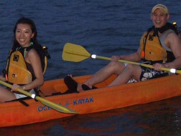 A couple in an orange kayak with yellow paddles smiling and kayaking at night
