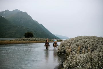 a person riding a horse in a body of water