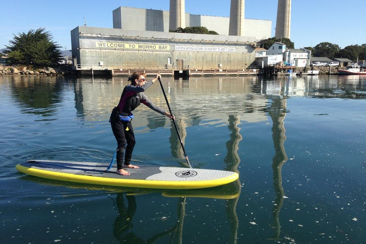 individual on paddleboard with Welcome to Morro Bay sign in the background