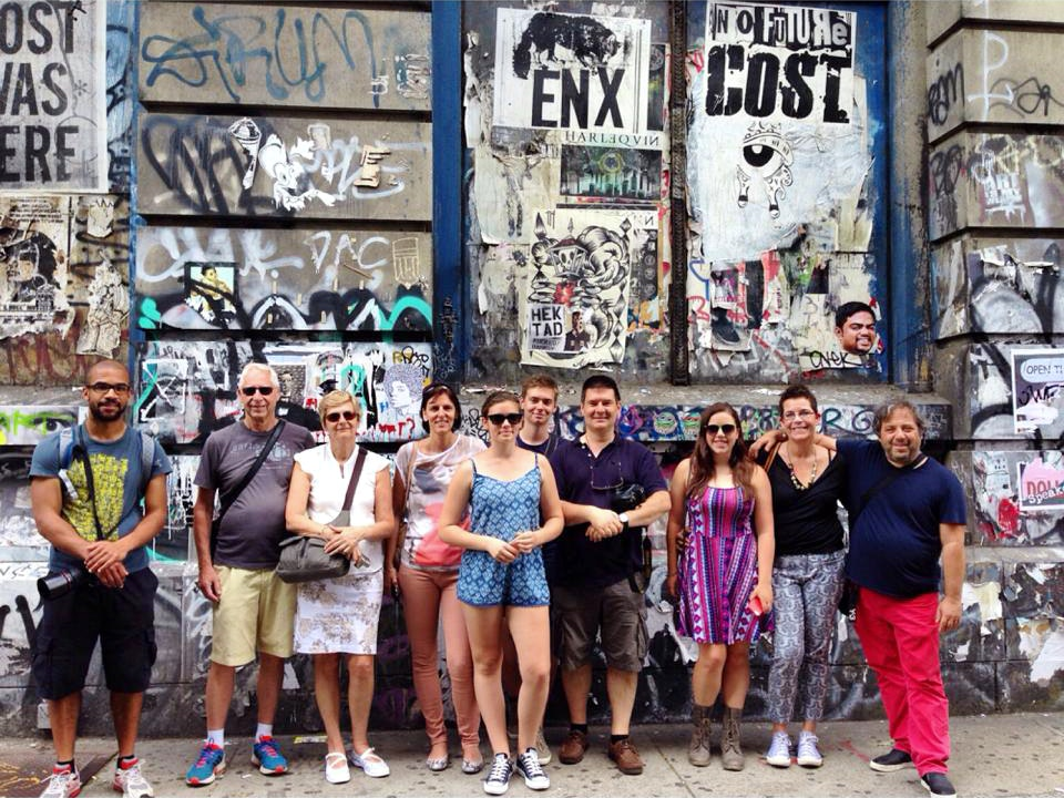 A Graff Tours group stops for a photo at the building's street art covered base.