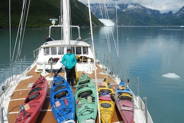 Kayaker standing on deck of boat with kayaks near Ailik Glacier in Alaska