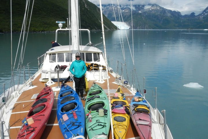 Kayaker standing on deck of boat with kayaks near Ailik Glacier in Alaska