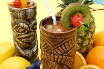 Tropical drinks in tiki mugs
