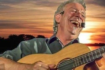 Man laughing and playing guitar
