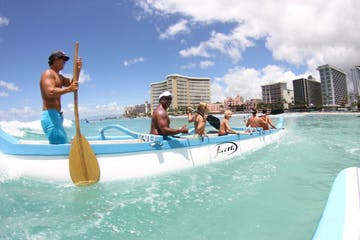 Catching surf on an outrigger canoe