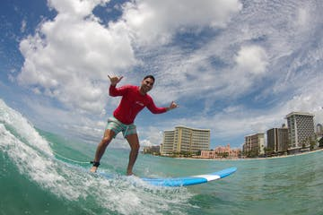 man in red shirt surfing and smiling for camera