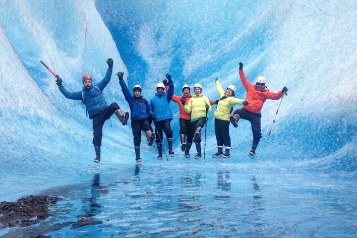 A group of tourists pose near a glacier in Alaska