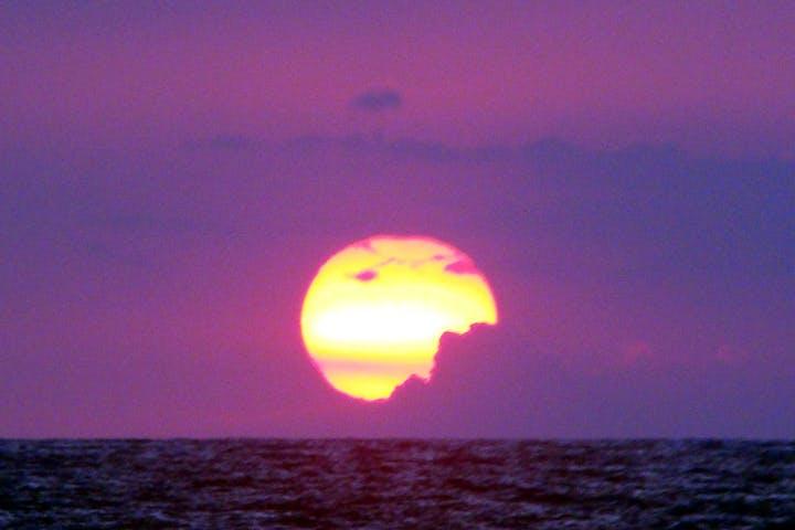 Purple sunset and bright yellow sun meeting the horizon along the Kona coast