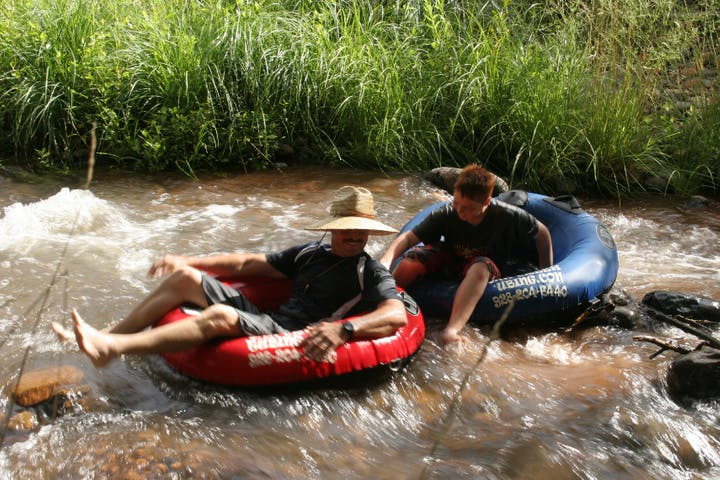 man with sunhat and child sitting in tubes in the river