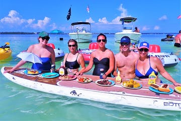 Line of people eating food off of paddleboard in the water