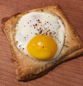 a piece of bread with egg on top of a wooden cutting board
