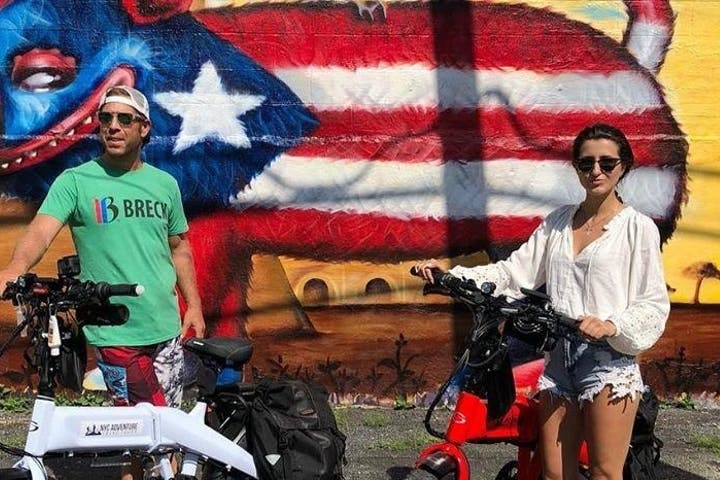 man and woman standing with ebike in front of mural