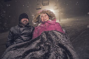 a happy couple getting cozy on a sleigh ride